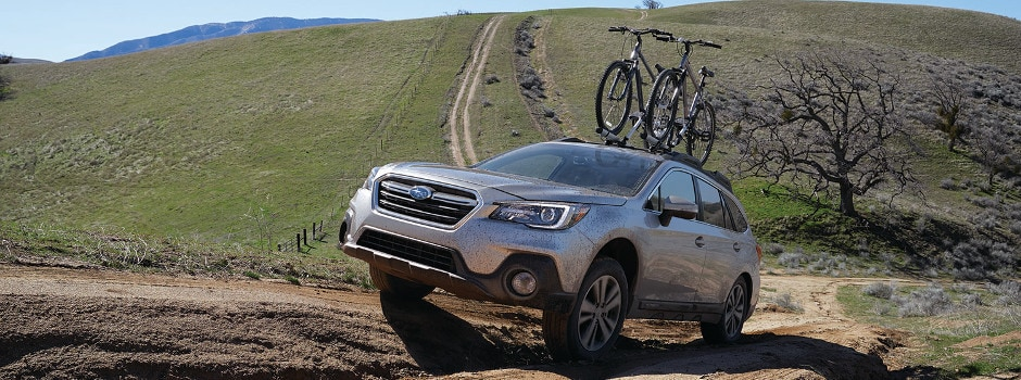 A silver Subaru Outback driving down a dirt road