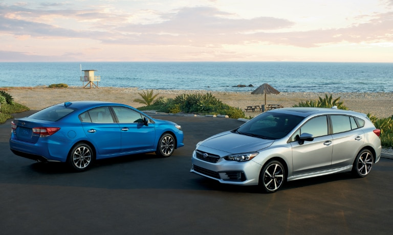 2020 Subaru Impreza in blue and hatchback in gray parked in parking lot with beach in the background
