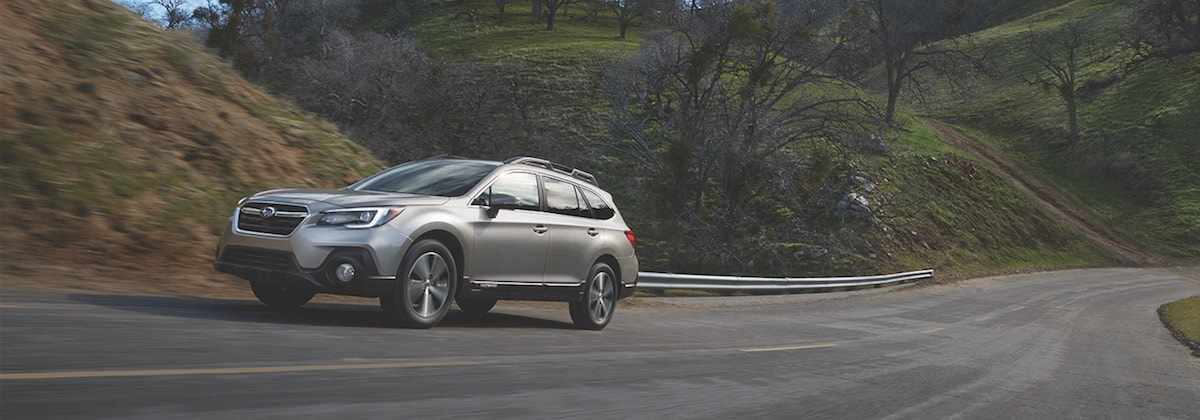 A 2019 Subaru Outback driving through grassy hills