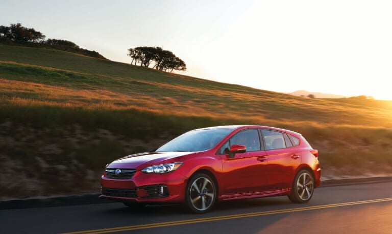 2020 Subaru Impreza in red driving on highway with hilly plans along it