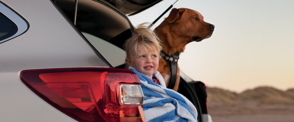 A child wrapped in a towel and a dog sitting in the back of the 2019 Subaru Outback
