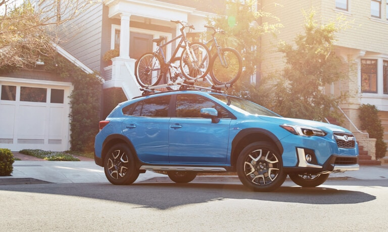 2020 Subaru Crosstrek in blue with loaded bike rack leaving driveway
