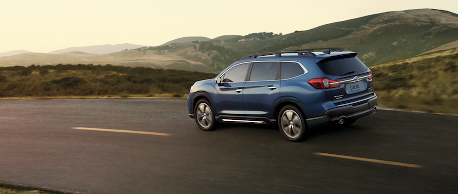 A blue 2019 Subaru Ascent driving through the mountains
