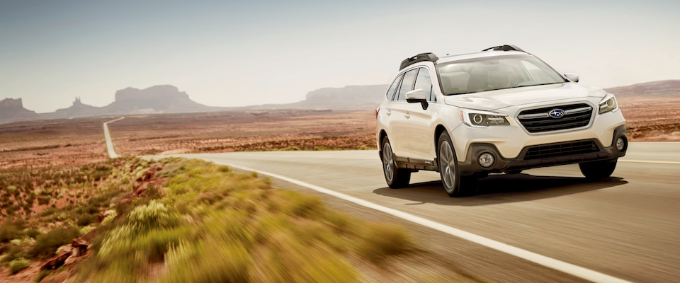 White Subaru Outback driving through the desert