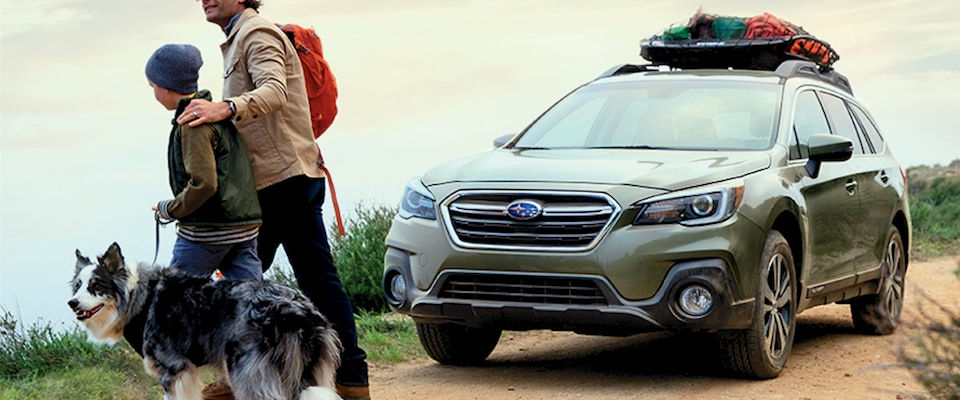 A father, son & doge walking in front of thei Subaru Outback