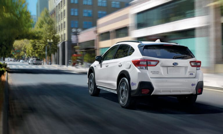 2020 Subaru Crosstrek in white driving on a city street in motion