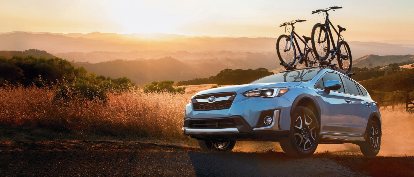 2020 Subaru Crosstrek in blue driving up dirt road in the in a open field