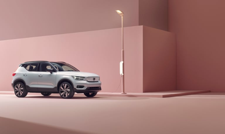 2020 Volvo XC40 Recharge in silver at a charging station with all pink walls and ground view from the front passanger side.jpg