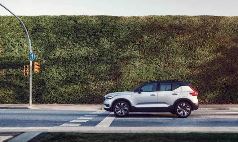 2020 Volvo XC40 Recharge in white stopped at red light with a large bush along the road
