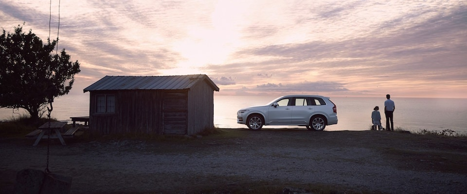 A Volvo XC90 parked by a lake at sunset