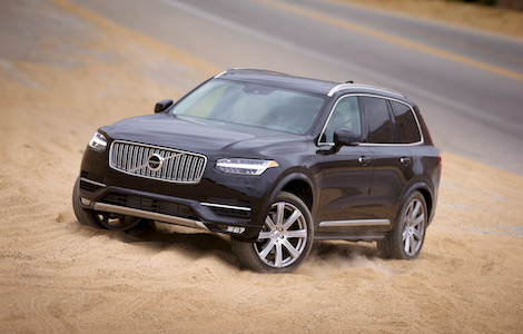 A black Volvo XC90 driving through the sand
