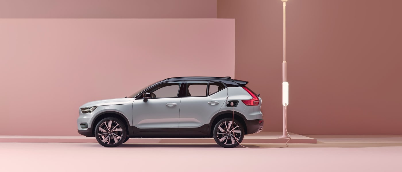 2020 Volvo XC40 Recharge in silver at a charging station with all pink walls and ground