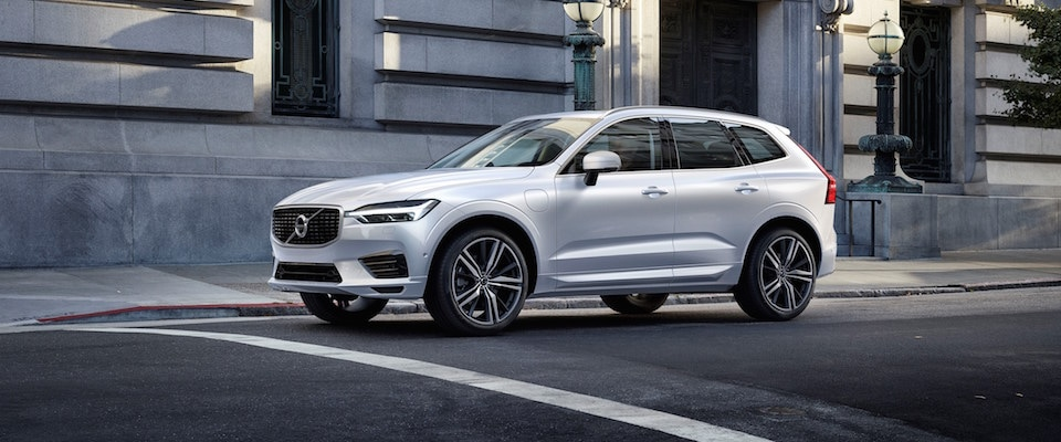 A silver 2019 Volvo XC60 parked on the street of a city