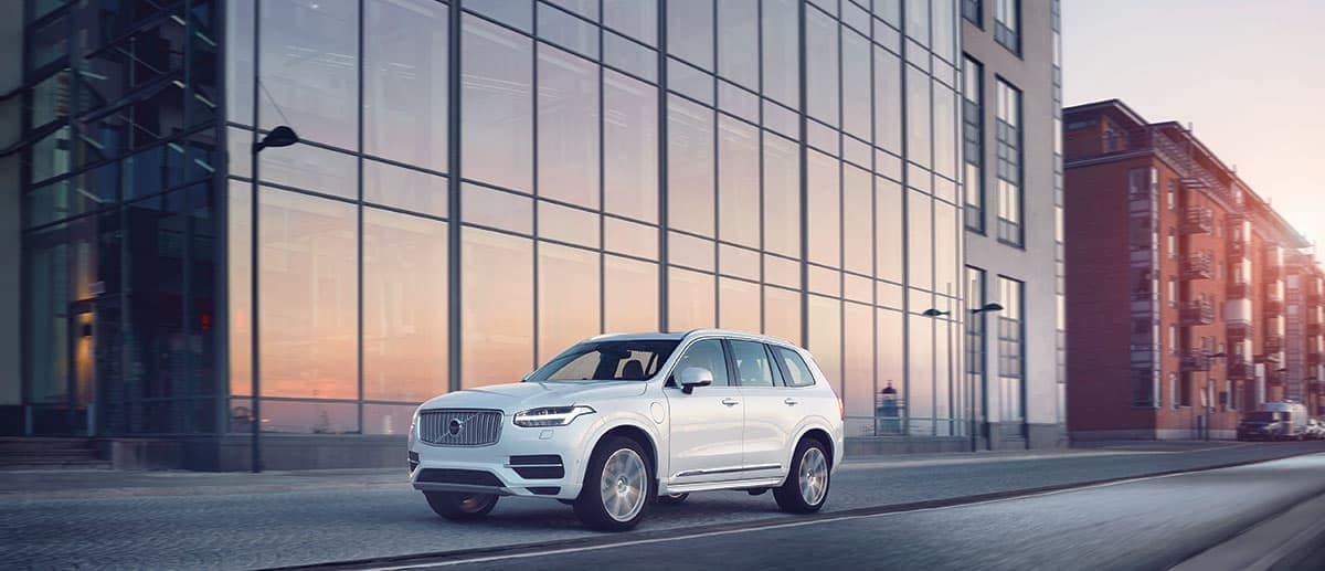 A white 2019 Volvo XC90 driving down a road