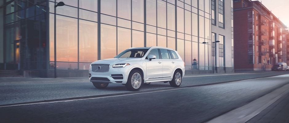 A white Volvo XC90 driving past a modern city building during sunset