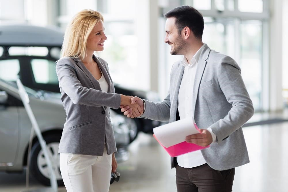 A Happy Customer Discussing Car Purchase Plans with a Top Car Dealer