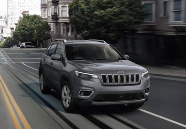 New 2019 Jeep Cherokee in a city with trees