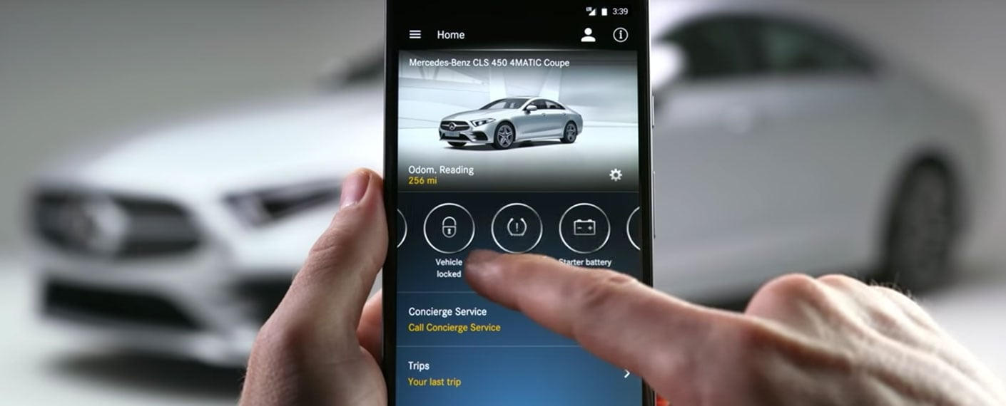 Mercedes me connect app screen on iPhone with Mercedes-Benz CLS in background