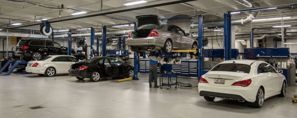 Inside a Mercedes-Benz service center with a service technician maintaining a vehicle