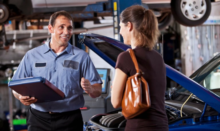 woman talking to mechanic while haveing vehicle getting looked at