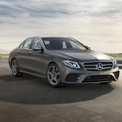The front passenger side of a dark silver 2019 Mercedes-Benz E-Class sedan parked on a tiled concrete platform with grassy hills and a cloudy blue sky in the background