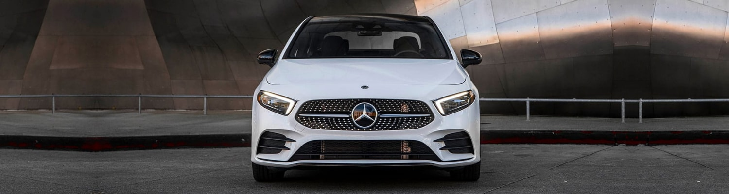Front angle of a white 2019 Mercedes A-Class sedan parked in front of a sidewalk with a shiny metal building behind the car
