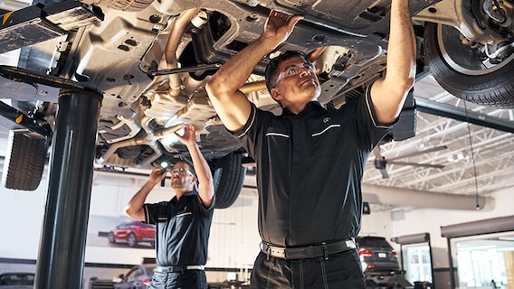 Mercedes-Benz technician performing repairs underneath a Mercedes-Benz vehicle