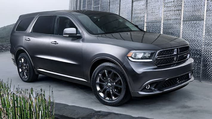 A silver Dodge Durango parked in front of a metal wall