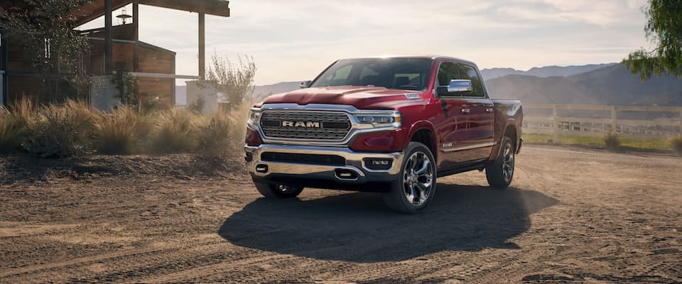 A red 2019 Ram 1500 driving on a dirt road near the mountains
