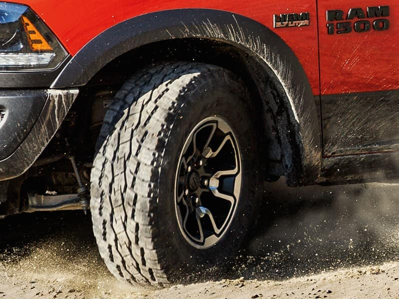 The tire of a red Ram 1500 driving through the dirt