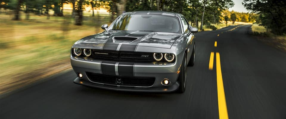 A silver 2019 Dodge Challenger driving down an open country road