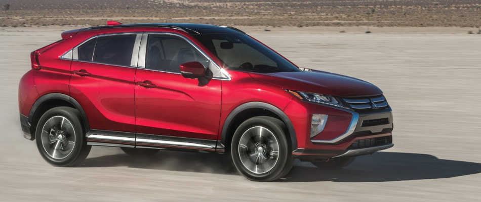 A red Mitsubishi Eclipse Cross driving through an open dirt road