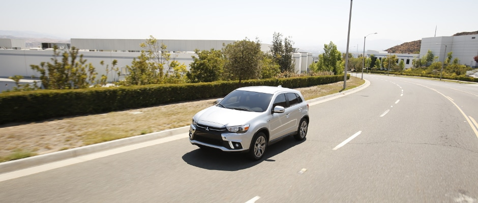 A white Mitsubishi Outlander Sport driving down a road on a nice day