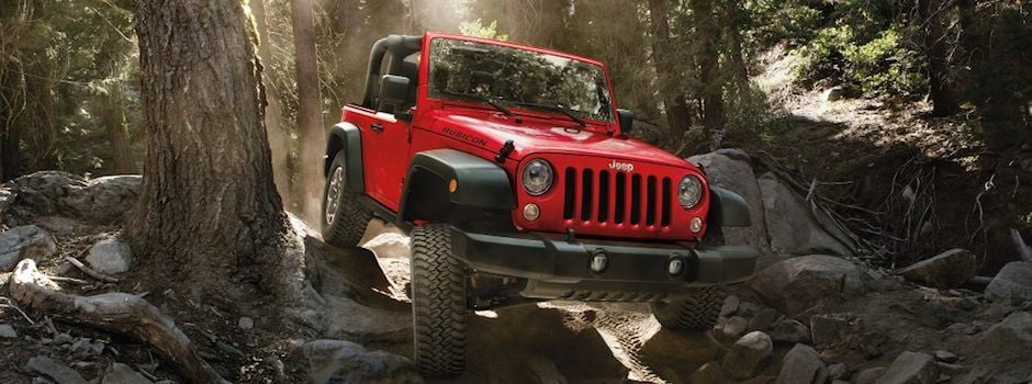 A red 2018 Jeep Wrangler driving through a rocky forest