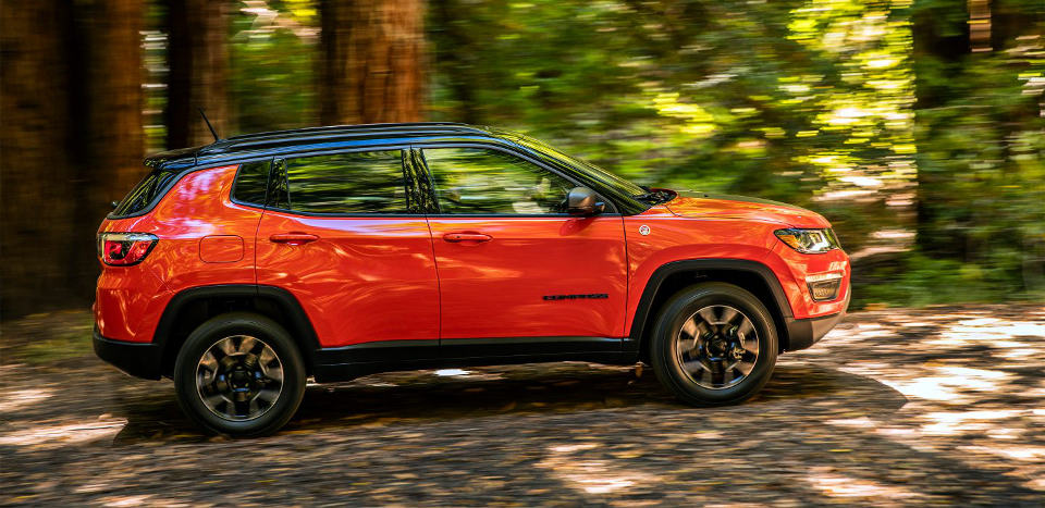 2017 Jeep Compass driving fast through a wooded area