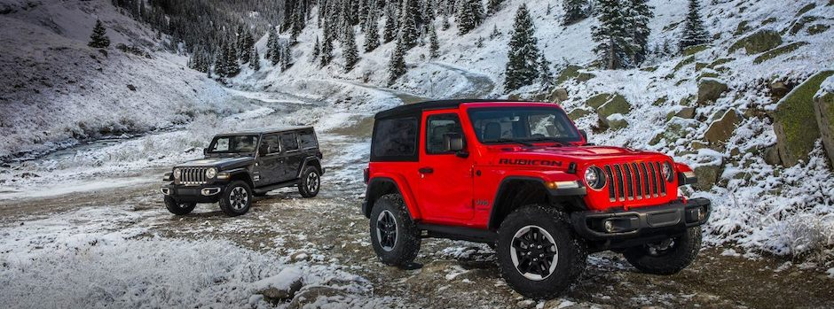 Two Jeep Wranglers parked by the mountains