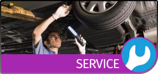 Graphical Button with the text Service, showing a mechanic inspecting a vehicle on a hydraulic lift, and a Wrench icon