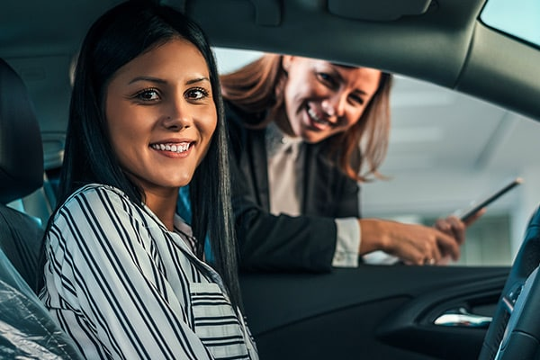 Young woman sitting in brand new car.