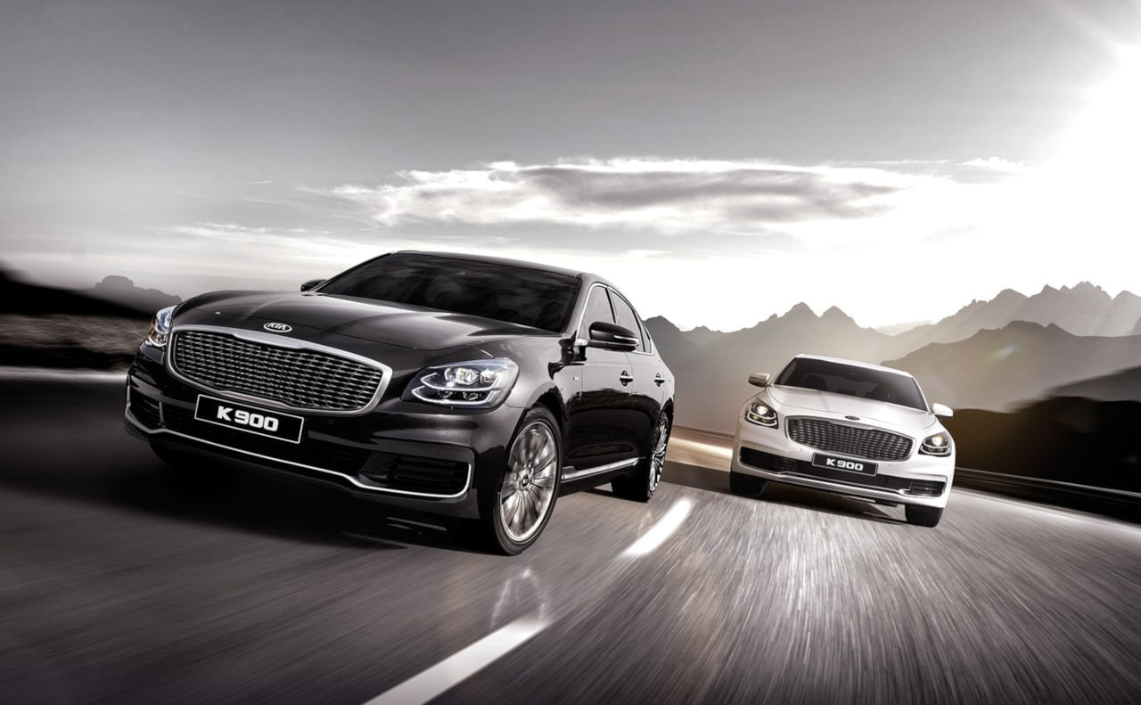 Two Kia K900 Luxury Sedans on Highway with Mountains