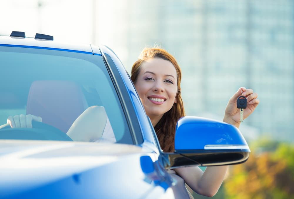 Woman holding up keys in new car