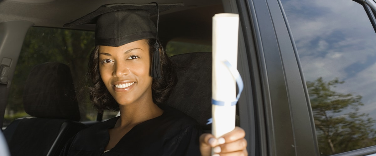 College Grad in cap and gown holds out diploma while sitting in a car