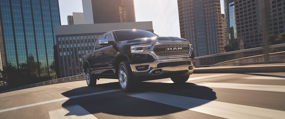 A black 2019 Ram 1500 driving down a city road
