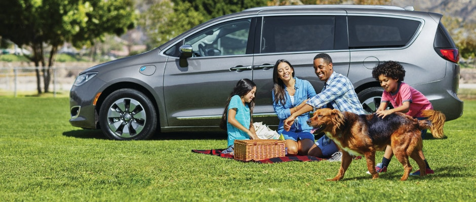 A family on a picnic with their Chrysler Pacifica