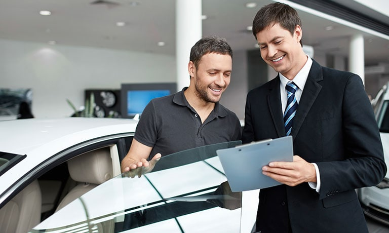 Man Looking over clipboard with sales rep