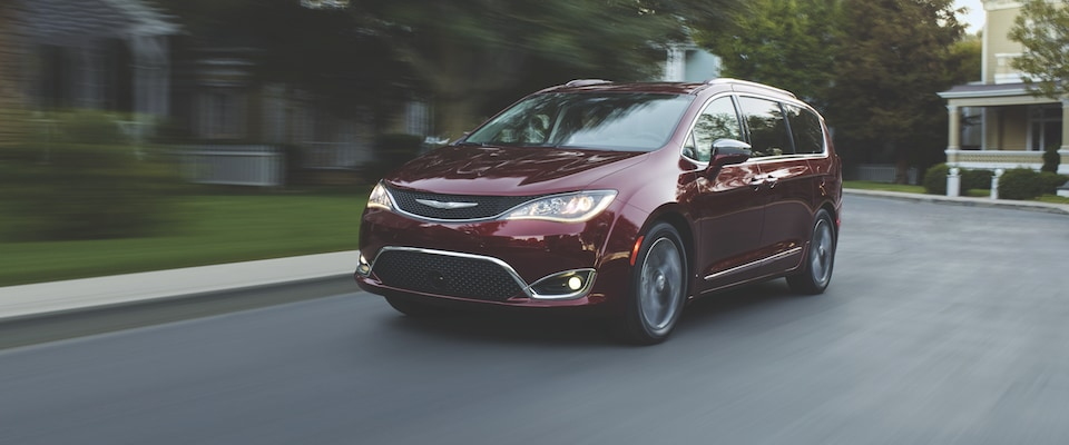 A Chrysler Pacifica driving through a suburban street