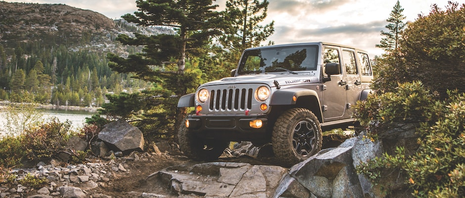 A 2013 Jeep Wrangler going offroading by a lake and mountains