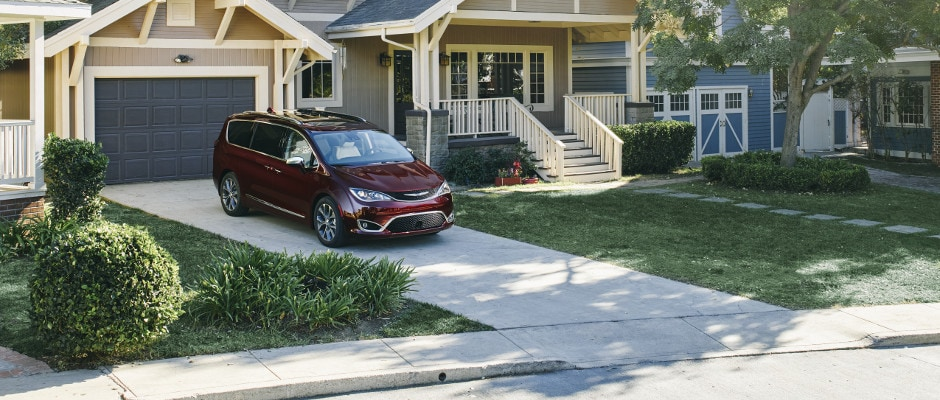 A red Chrysler Pacifica parked in a driveway of a suburban home