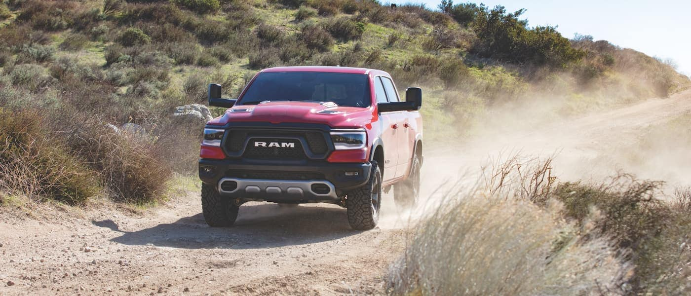 2020 Ram 1500 in red driving on a dirt hill