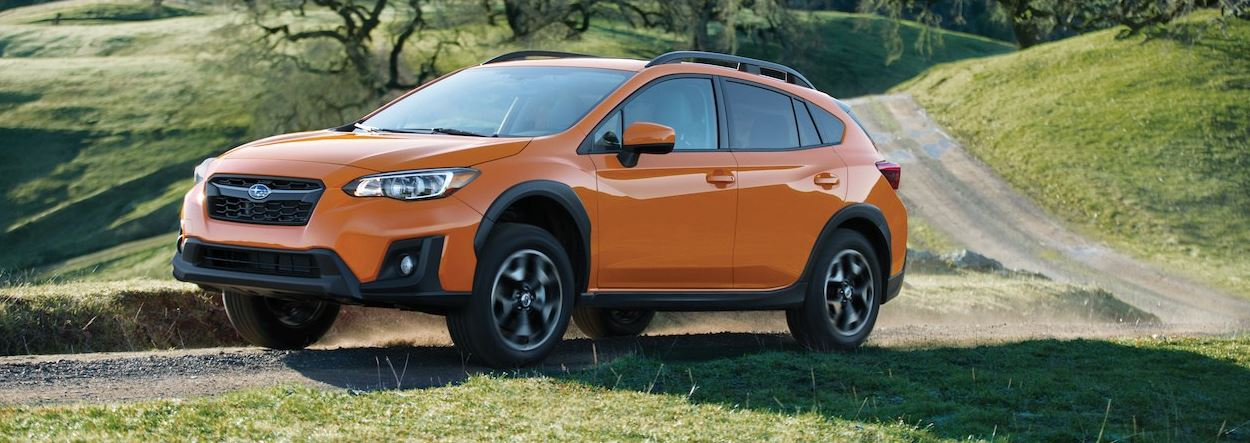 orange subaru on a hill