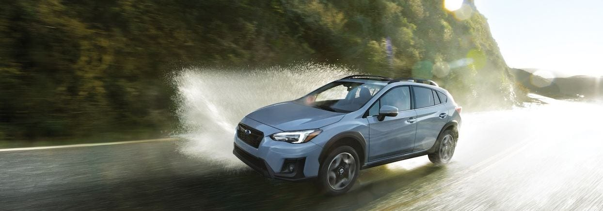 Subaru driving on wet roads